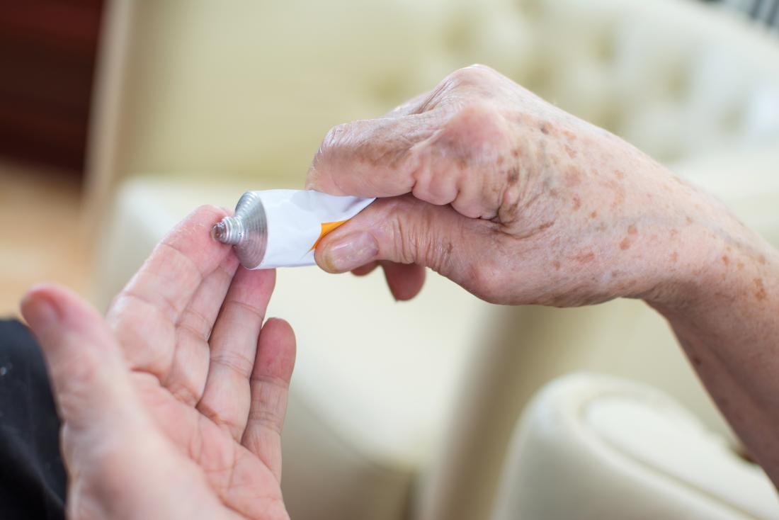 close up of seniors hands squeezing ointment from tube