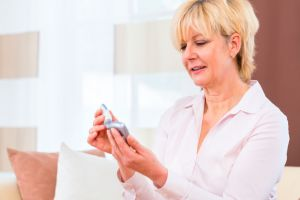 Woman checking her blood sugar with glucose meter