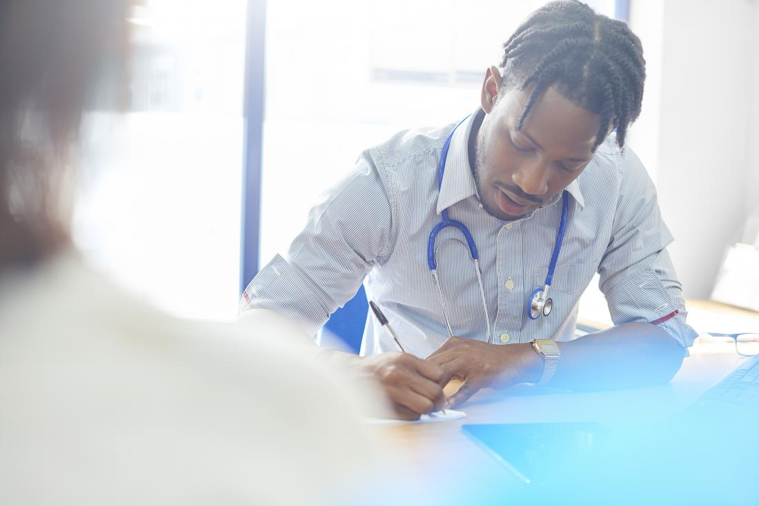 Doctor speaking to his patient and writing a prescription