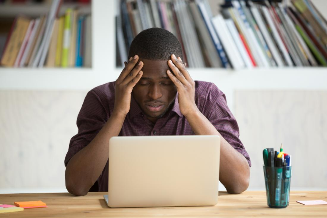 Frustrated man with his head in his hands in front of his laptop