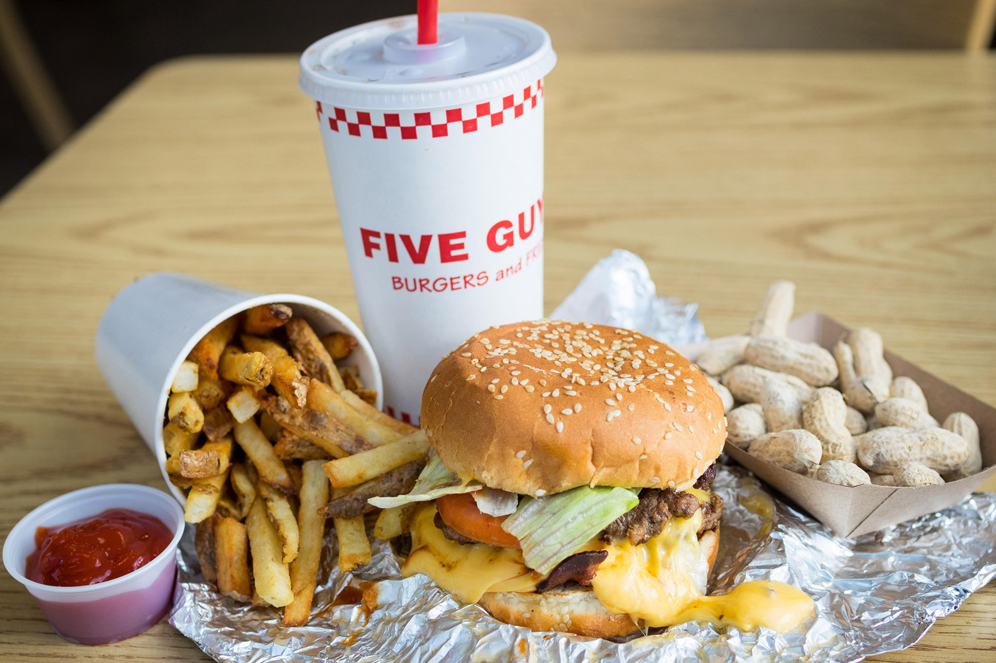 A bacon cheeseburger, French fries, and peanuts from Five Guys Burgers and Fries, an American fast casual restaurant chain.