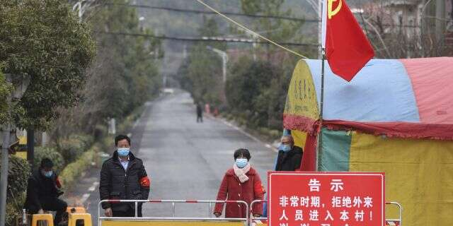 Volunteers stand beneath a Communist Party flag as they man a barricade checkpoint at a village in Hangzhou in eastern China's Zhejiang Province, Monday, Feb. 3, 2020. (Chinatopix via AP)