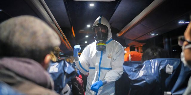 A military officer wearing a protective suit gives instructions to evacuees from Wuhan, China, as they travel to a hospital after their arrival at a military base in Wroclaw, Poland, on Feb. 2, 2020. (AP Photo/Arek Rataj, File)