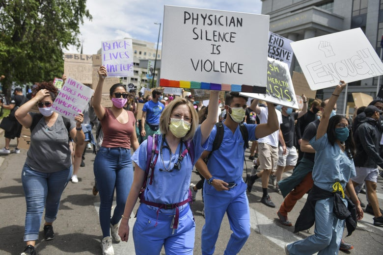 """Physicians in scrubs march in support of protests against police brutality, holding a sign that says """"physician silence is violence."""""""