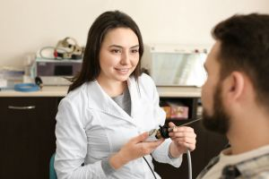 A student audiologist gives a hearing exam.