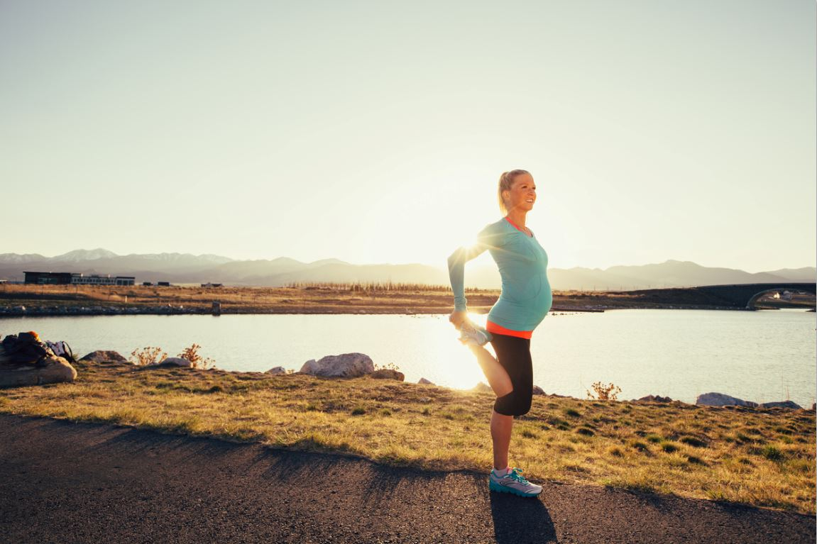 pregnancy and exercise woman stretching and jogging outdoors